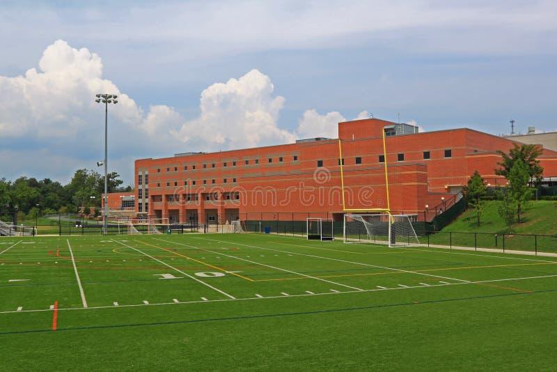 Edificio scolastico con il campo di football americano fotografie stock