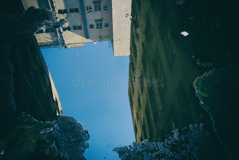 Edificio sucio dilapidado reflejado en un charco imágenes de archivo libres de regalías