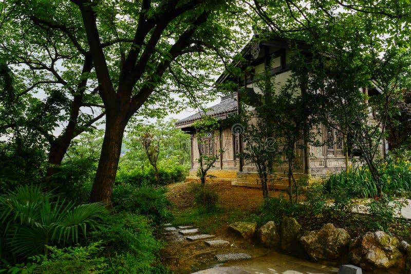 edificio Teja-cubierto del timberwork detrás de árboles en la primavera nublada af fotografía de archivo