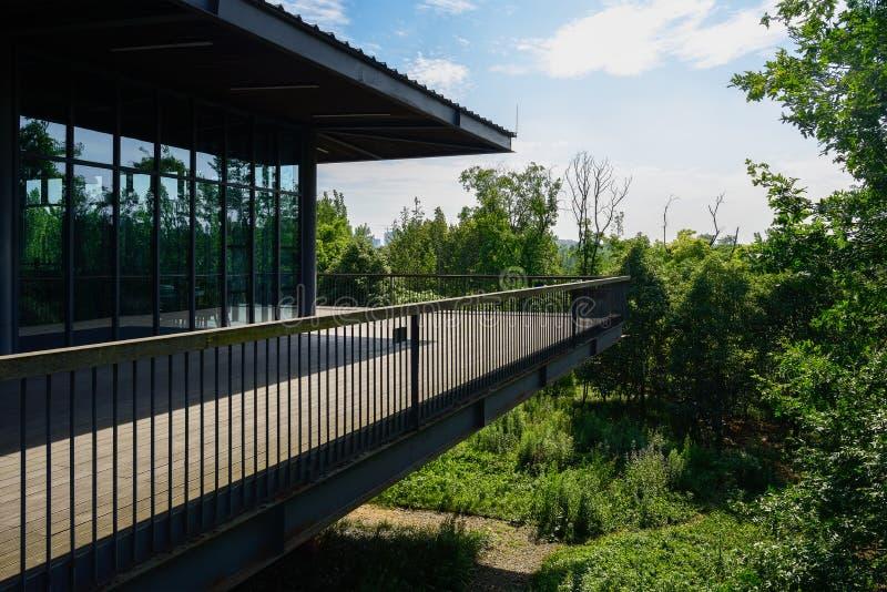 edificio Vidrio-emparedado en la plataforma planked con la verja de acero adentro imagen de archivo