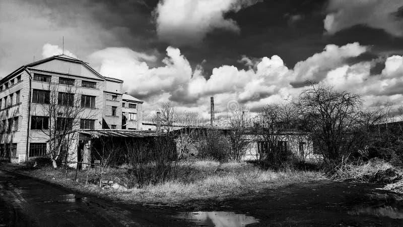 Edificio viejo abandonado de la fábrica debajo del cielo dramático nublado fotografía de archivo libre de regalías