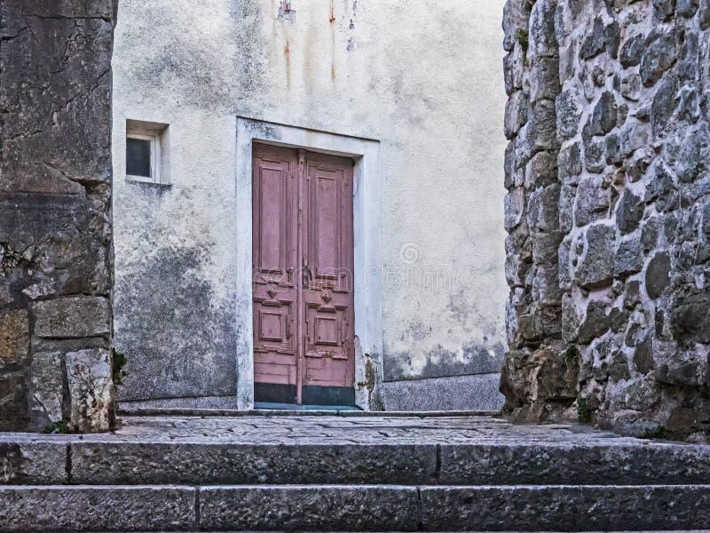 Edificio viejo con la puerta roja en la ciudad vieja de la ciudad Rab en la isla croata Rab imagen de archivo libre de regalías