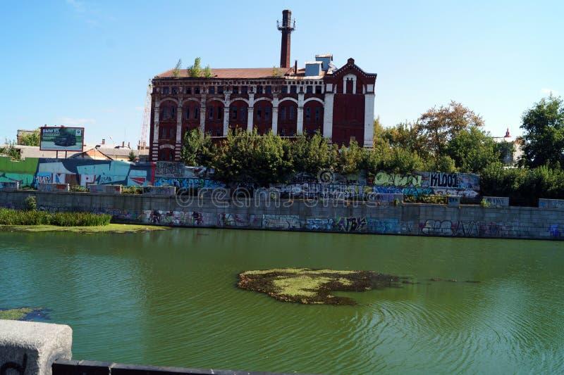 Edificio viejo de la fábrica cerca del río imagen de archivo libre de regalías