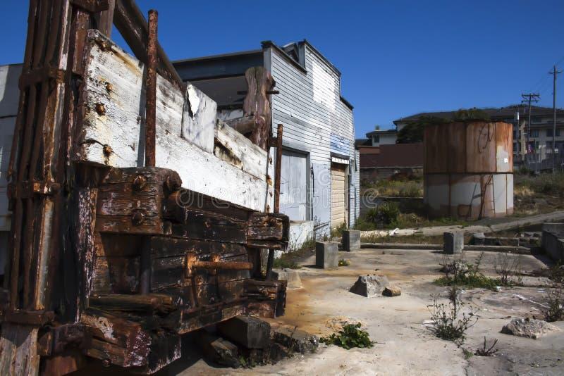 Edificio viejo de la fábrica de conservas con la tolva aherrumbrada del tanque y de los pescados en fila de la fábrica de conserv fotos de archivo
