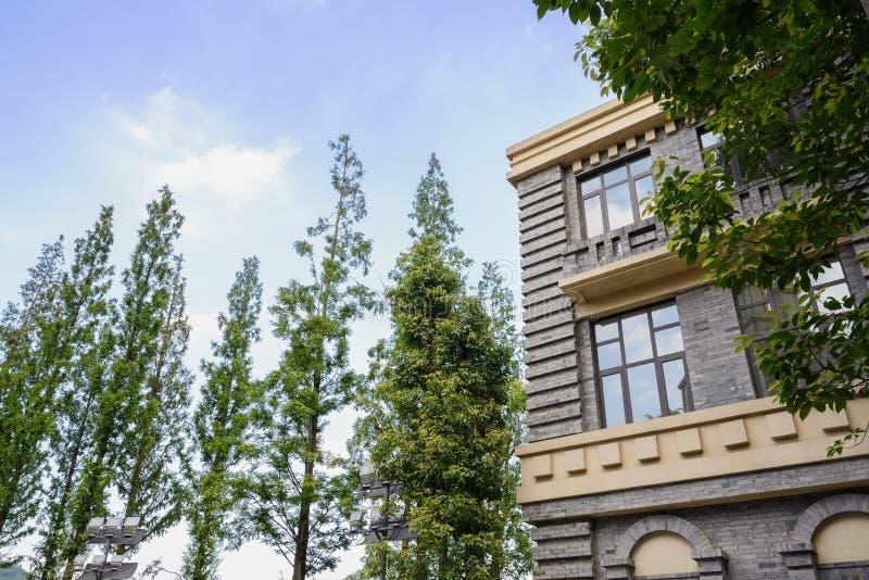 Edificio y árboles europeos del estilo en cielo soleado imagenes de archivo