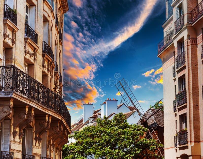 Edificio y molino de viento elegantes en la vecindad de Montmartre en los soles imagenes de archivo