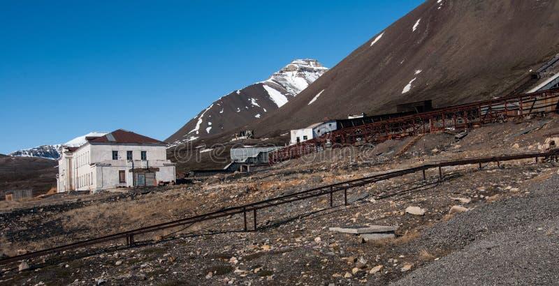 Edificios abandonados usados para minar y el transporte del carbón en el pueblo fantasma ruso soviético Pyramiden en Svalbard imágenes de archivo libres de regalías