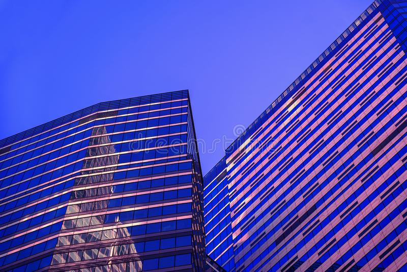 Edificios abstractos en la noche, el modelo geométrico de cristal y de concreto, de gran altura, diseño con la reflexión Edificio foto de archivo