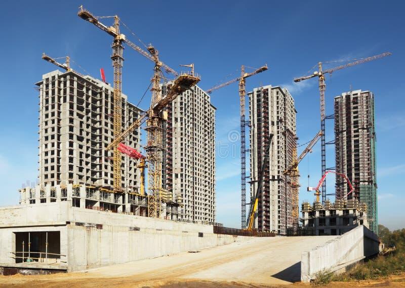Edificios altos bajo construcción con las grúas foto de archivo libre de regalías