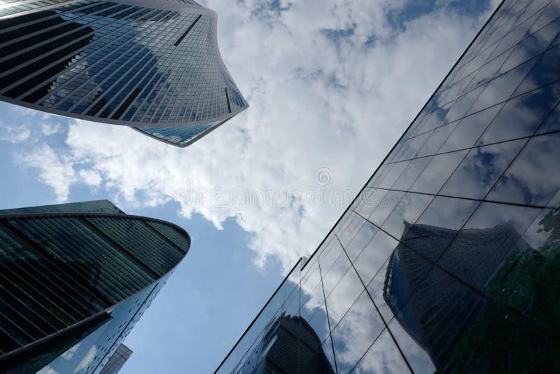 Edificios altos del desplome de cristal y concreto en el cielo con las nubes fotografía de archivo