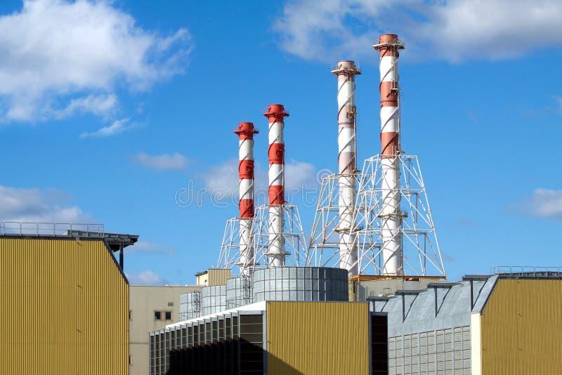 Edificios de la central eléctrica con los altos tubos del humo fotografía de archivo