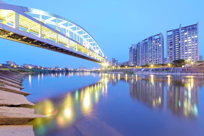 Edificios de la orilla y el puente famoso del arco iris de HuanDong sobre el río de Keelung en la oscuridad en Taipei Taiwán, Asi foto de archivo