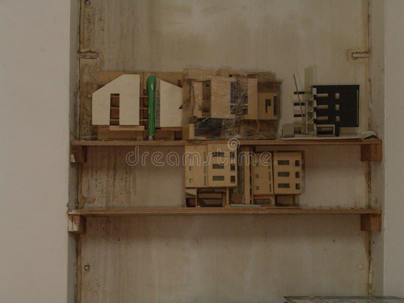 Edificios de madera miniatura en la exhibición en un estante de madera contra una pared fotos de archivo