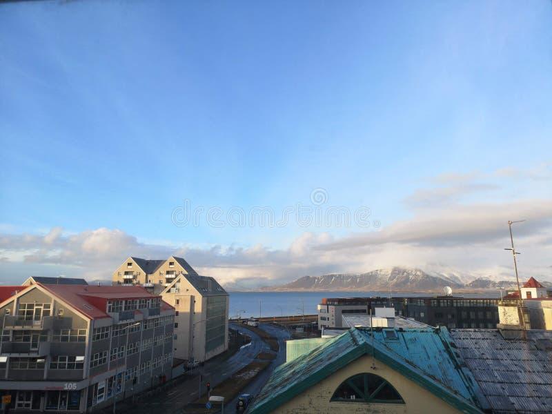 Edificios de Reykjavik, camino, océano y Mountain View foto de archivo libre de regalías