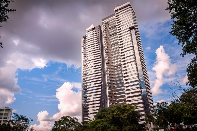 Edificios debajo del edificio skymodern azul en el medio del cielo fotos de archivo