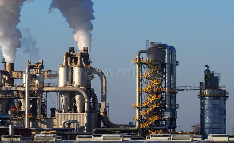 Edificios industriales con las pilas de humo, los tubos, las escaleras y los silos imagen de archivo