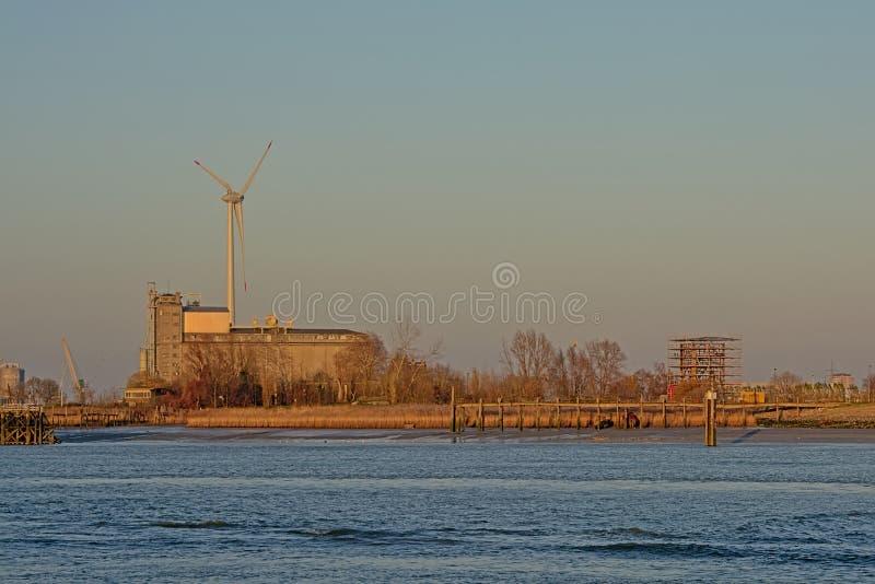 Edificios industriales y turbina de viento viejos a lo largo de un muelle en el puerto de Amberes foto de archivo libre de regalías