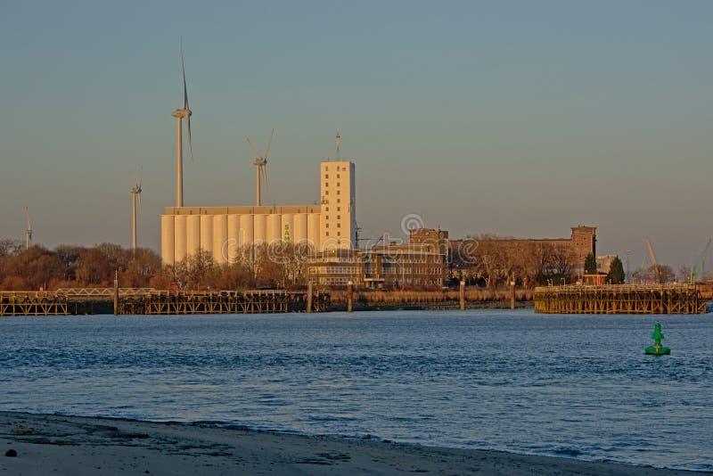 Edificios industriales y turbina de viento viejos a lo largo de un muelle en el puerto de Amberes foto de archivo