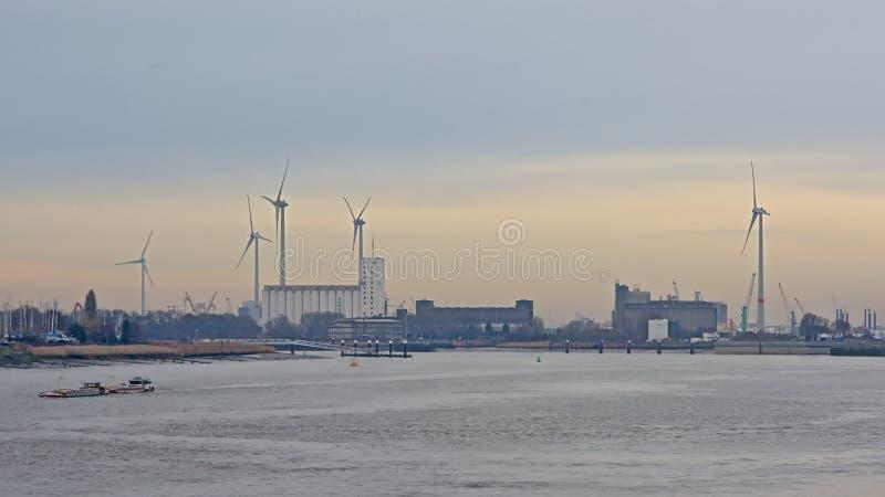 Edificios industriales y turbinas de viento en un muelle en el puerto de Amberes fotos de archivo libres de regalías
