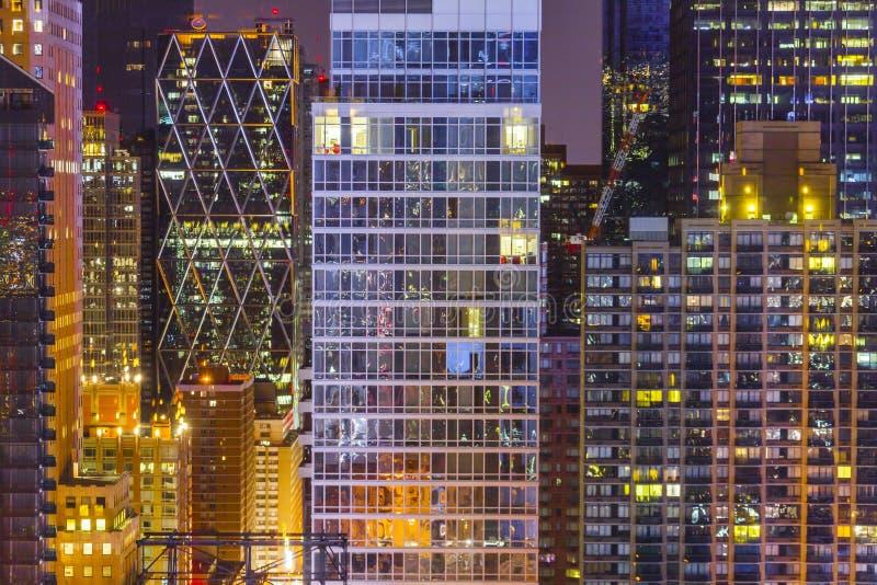 Edificios oficinas apartamentos nocturnos con luces encendidas en algunos negocios privados inmobiliarios fotos de archivo