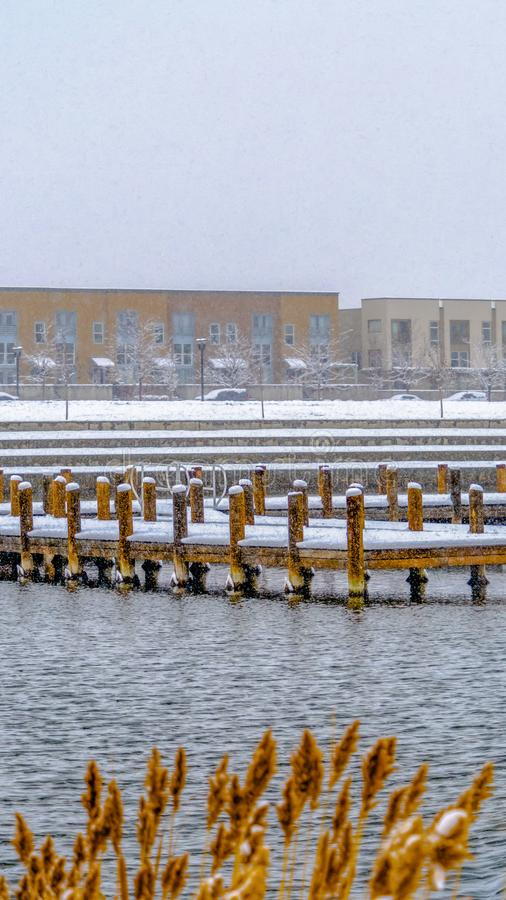Edificios verticales claros contra el cielo en un paisaje nevado más allá del lago en invierno fotos de archivo libres de regalías