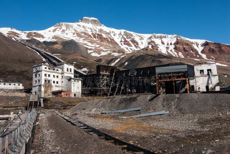 Edificios viejos usados para la explotación del cabón y el transporte del carbón en el pueblo fantasma ruso soviético Pyramiden e fotos de archivo libres de regalías