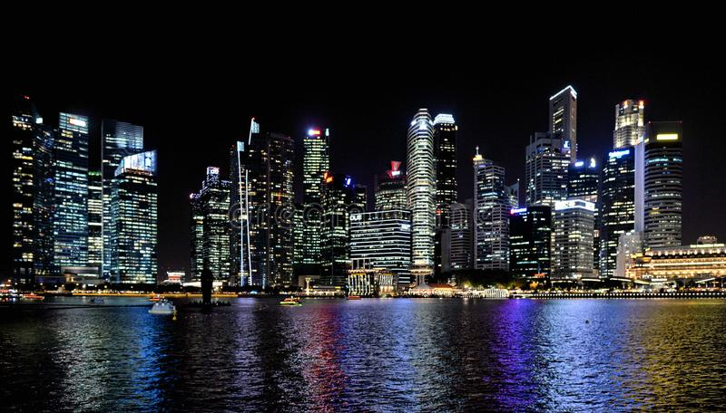 Edificios y luces en el mar y arquitecturas abstractas y horizonte modernos de la noche en Singapur fotografía de archivo libre de regalías