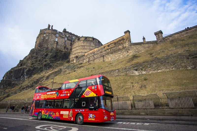 Edimburgo, Escócia Reino Unido - 19 de dezembro de 2016: Ônibus superior aberto do curso que passa através do castelo Escócia de  fotografia de stock royalty free