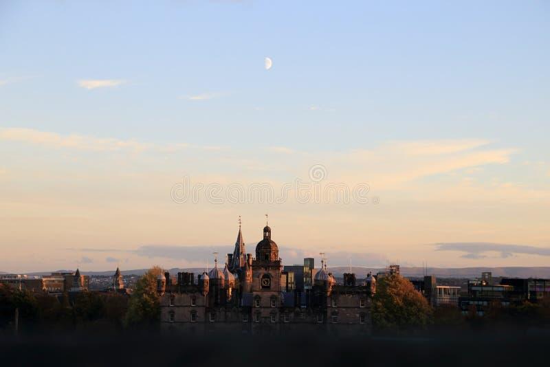 Edimburgo, Escocia Mirada de la opinión del paisaje urbano del castillo de Edimburgo por la tarde que ve la luna sobre edificios  imagen de archivo libre de regalías