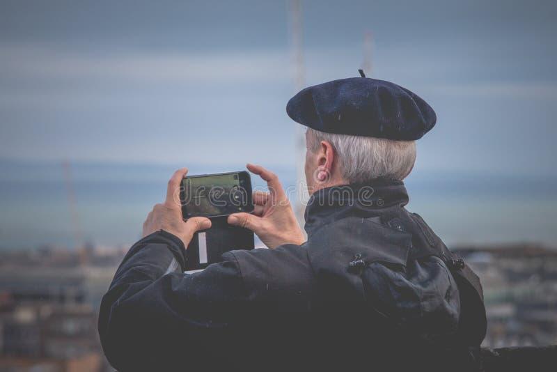 Edimburgo, Reino Unido - 10 de fevereiro de 2018 Homem do turista que toma imagens panorâmicos em Edimburgo, Escócia fotos de stock royalty free