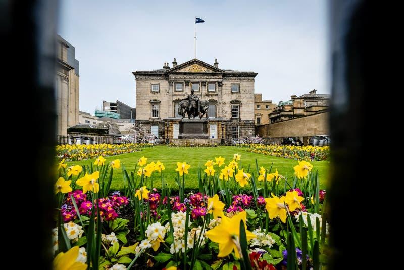 Edinburg Skottland - April 27, 2017: Högkvarter av den kungliga banken av Skottland som ses till och med staketet, med blomman royaltyfri foto