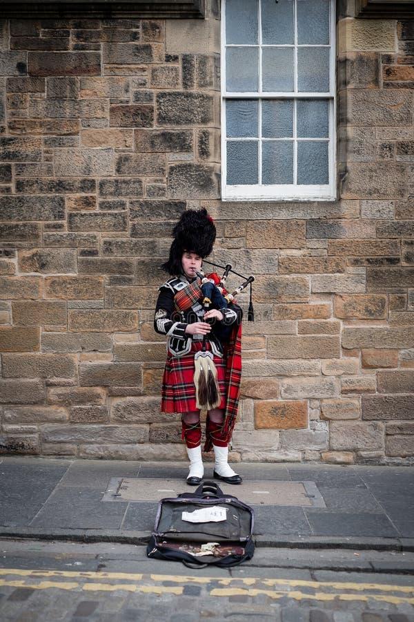 Edinburg Skottland - April 27, 2017: Säckpipe- spelare med traditionella skotska högländareämbetsdräkter som spelar på den kungli royaltyfria bilder