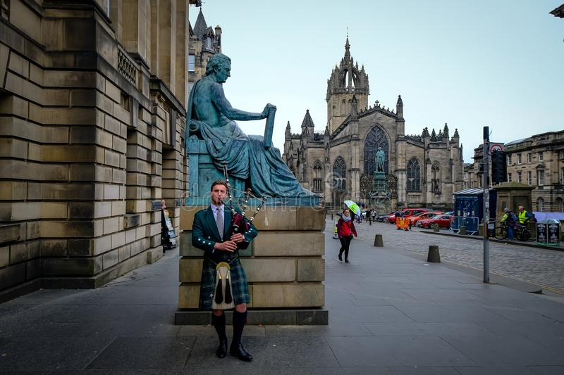 Edinburgh, Scotland - April 27, 2017: Bagpipe player with traditional scottish highlander robes playing on the Royal. Mile, with St. Giles catherdral in the stock photography