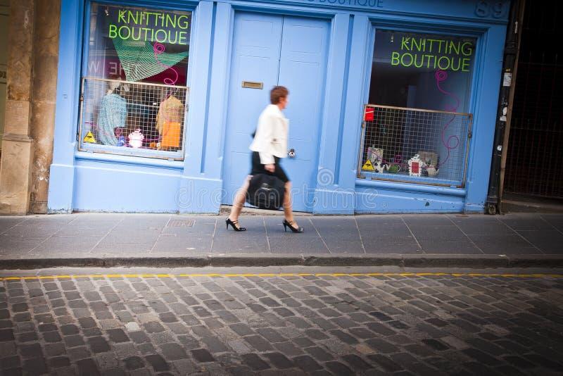 Edinburgh, Scotland - August 11, 2010: Defocused business woman walked fast on the street ramp of the castle stock image