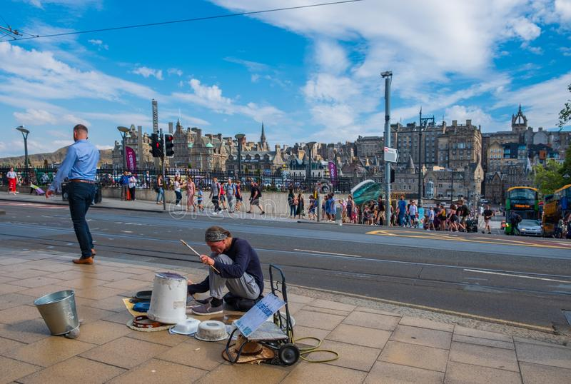 A street musician employing everyday utensils as drums performis on Princes Street. Edinburgh, United Kingdom - July 27, 2018: A street musician employing royalty free stock image