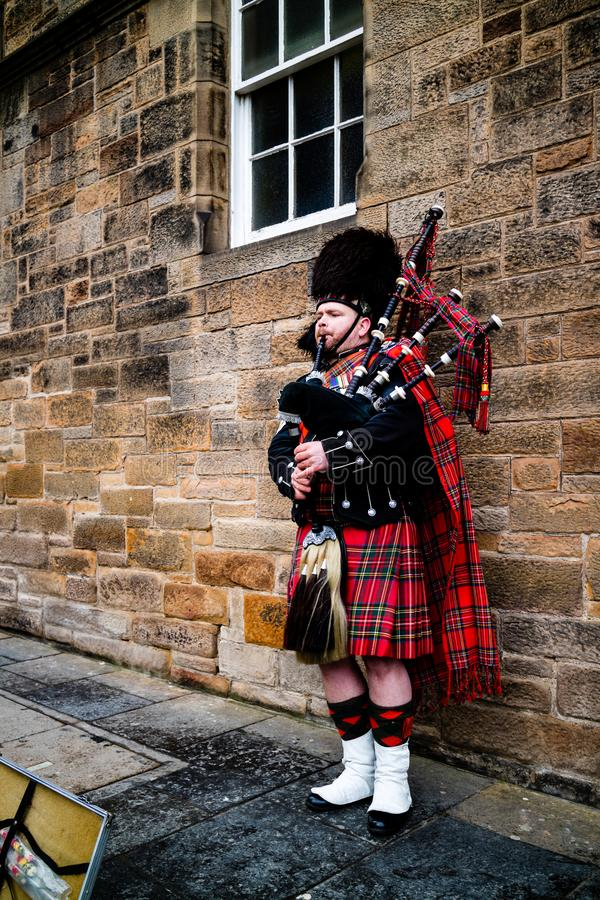 Edinburgh, United Kingdom - 01/19/2018: A man in traditional Scottish clothing playing the bagpipes. In front of a brick wall royalty free stock images