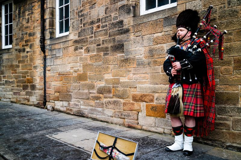 Edinburgh, United Kingdom - 01/19/2018: A man in traditional Scottish clothing playing the bagpipes. In front of a brick wall royalty free stock photos