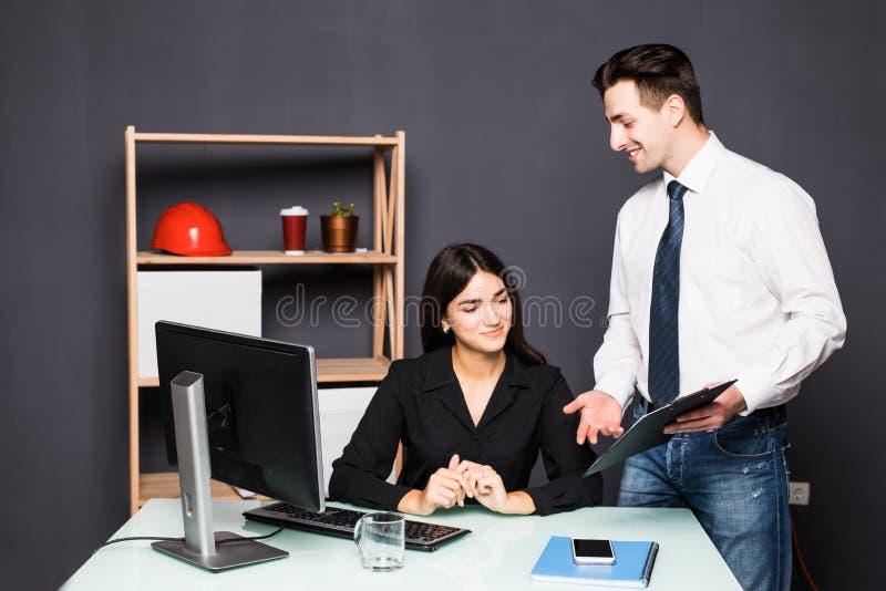 Editor de fotos atrativo que aponta na tela ao trabalhar com um colega no escritório fotos de stock royalty free