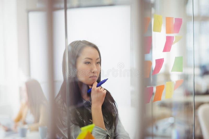 Editor de fotos pensativo que olha multi notas pegajosas coloridas no vidro imagem de stock