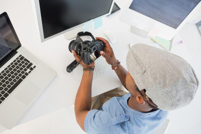 Editor de fotos que olha a câmara digital no escritório imagem de stock royalty free
