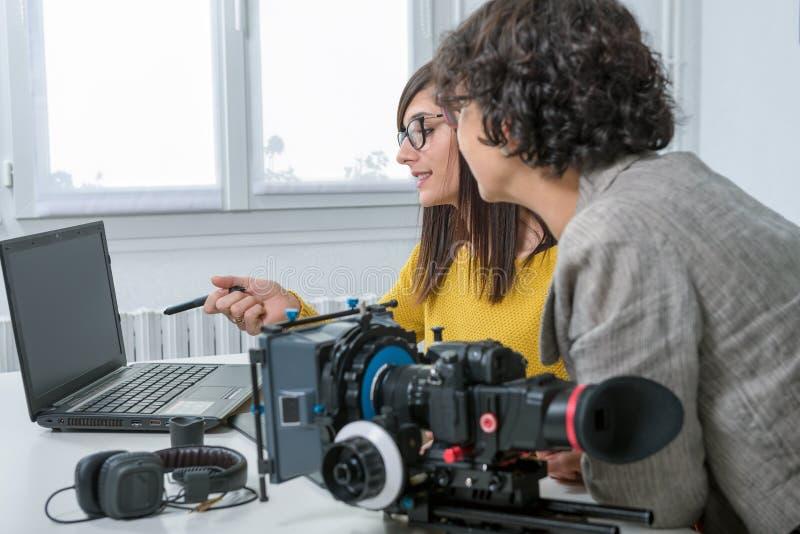 Editor de vídeo de la mujer y ayudante joven que usa la tableta gráfica foto de archivo
