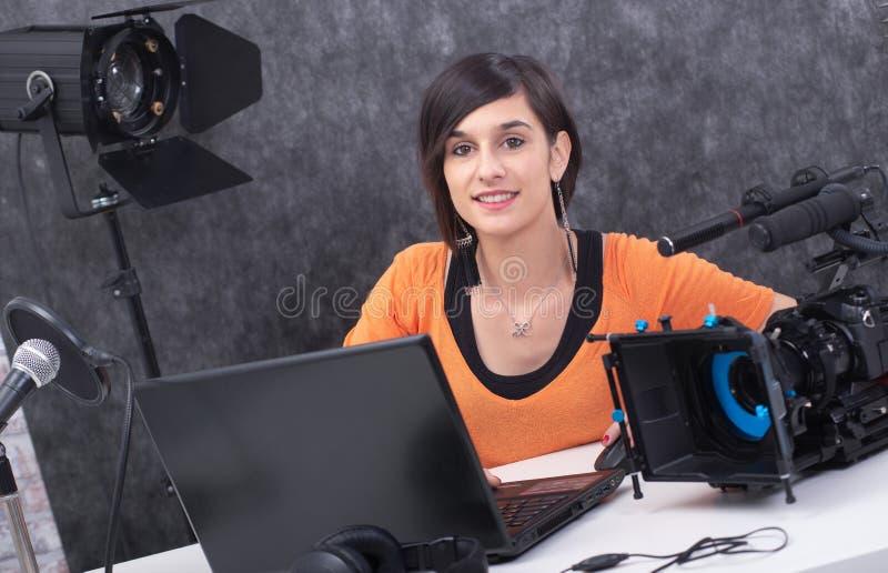 Editor de v?deo de la mujer joven que trabaja en estudio foto de archivo