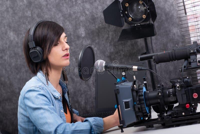 Editor de v?deo de la mujer joven que trabaja en estudio fotografía de archivo