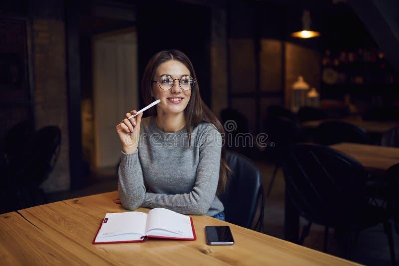 Editor fêmea que prepara a informação para o compartimento criativo ao pensar sobre algum positivo após o dia do trabalho duro imagens de stock