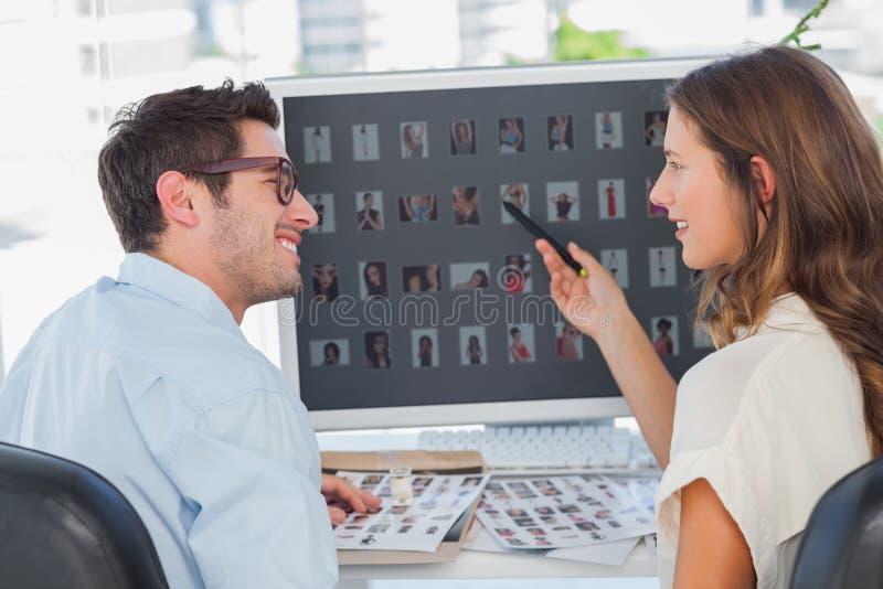 Editores de fotos alegres que trabalham nas unhas do polegar imagem de stock royalty free