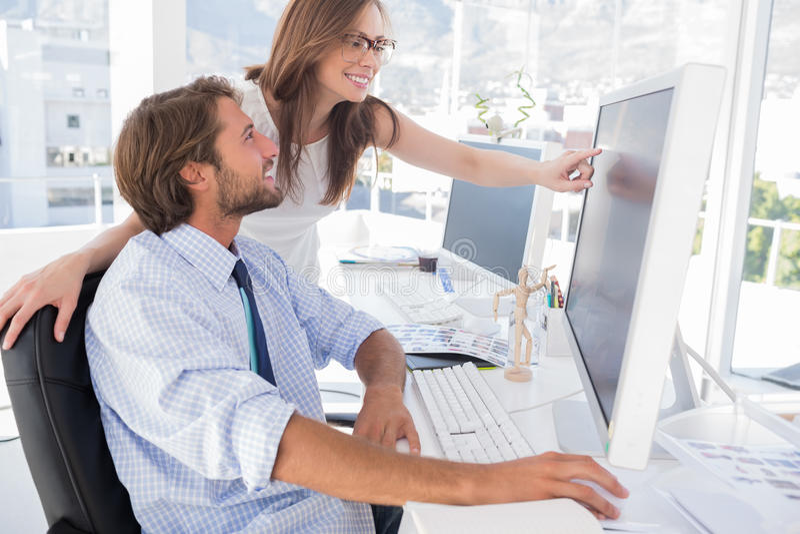 Editores de fotos que olham o ecrã de computador com o um que aponta imagens de stock royalty free