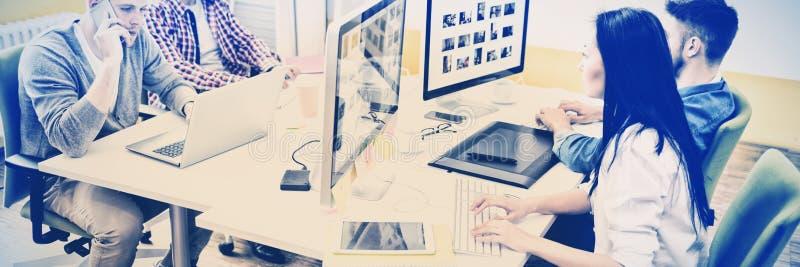 Editores de fotos que trabalham no escritório criativo imagem de stock royalty free