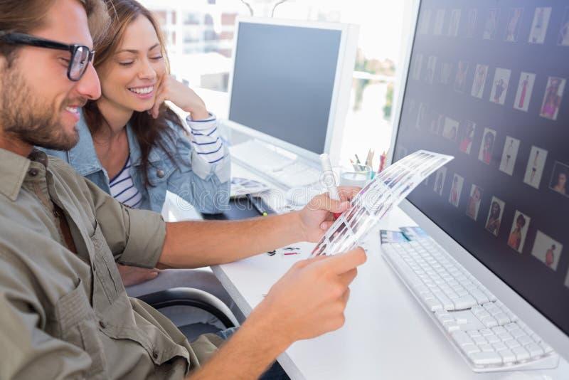 Editores de fotos que ven feliz la hoja del contacto fotos de archivo