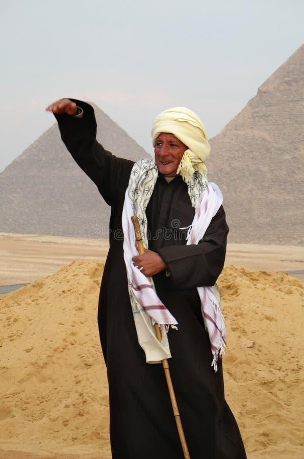 editorial cairo Giza valley/styczeń 05 2008: Stary człowiek w krajowym kostiumu mówi opowieść Ostrosłupy są na tle obrazy stock