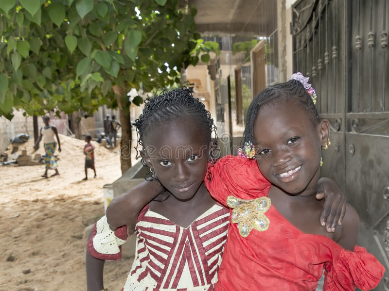 Editorial caption: M'BAO, SENEGAL, AFRICA – AUGUST 6, 2014- Two friends in the street on a feast day stock photos
